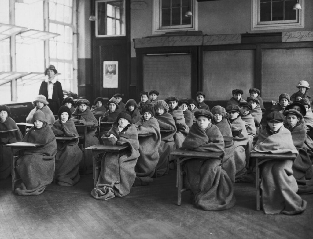 Pupils at a New York school enjoy the benefits of fresh air in the classroom, circa 1925.