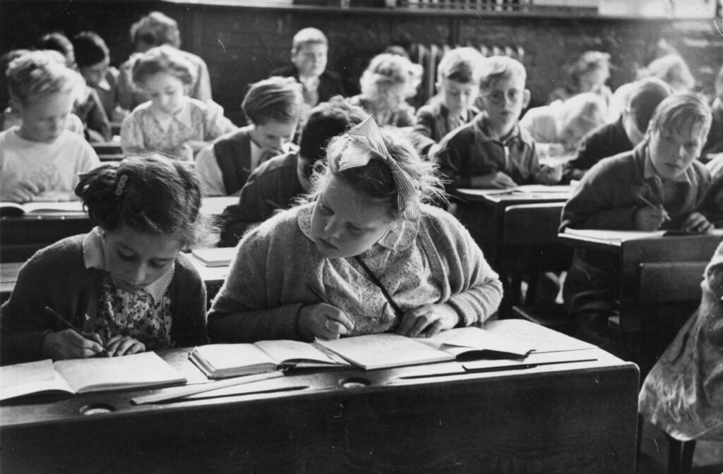 A schoolgirl copies notes from her friend's book in a classroom of Walsgrave Colliery Schoo