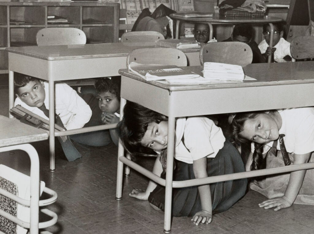 Students at a Brooklyn middle school have a 'duck and cover' practice drill in preparation for a nuclear attack; silver print, 1962. From the New York World-Telegram archive. (Photo by GraphicaArtis/Getty Images)