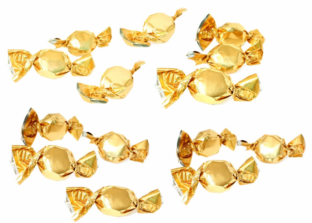 Candy with golden foil wrapper against white background