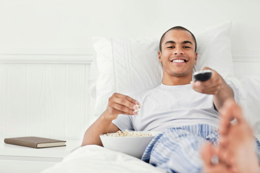 Young Man Watching TV in Bed