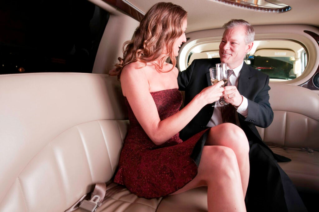 A businessman and his young companion enjoy a glass of champagne in a limousine.