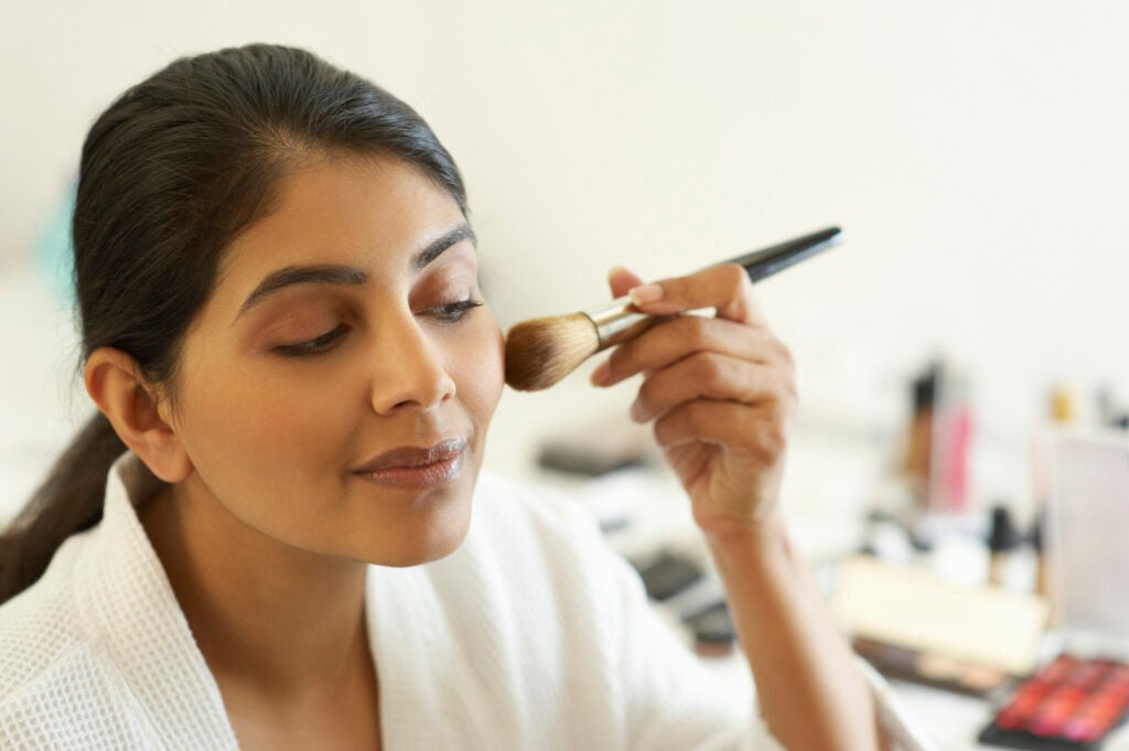 Asian woman applying make up with brush.