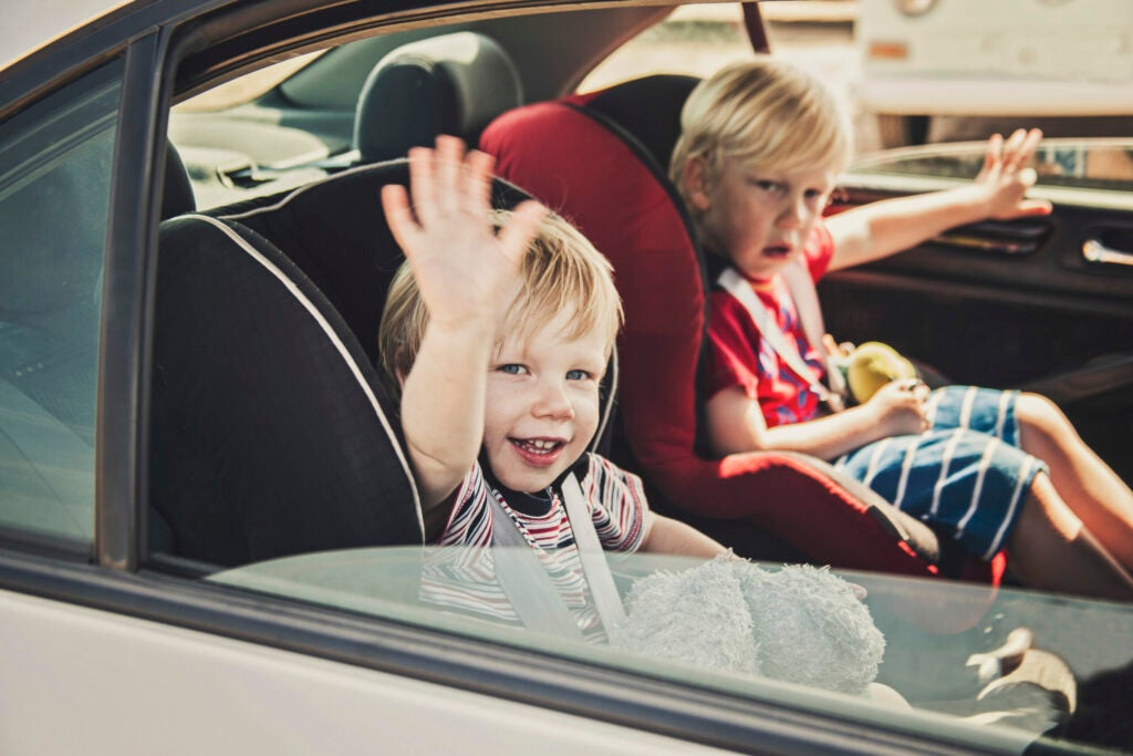 Happy smiling little boy waving while sat in the back of the car.