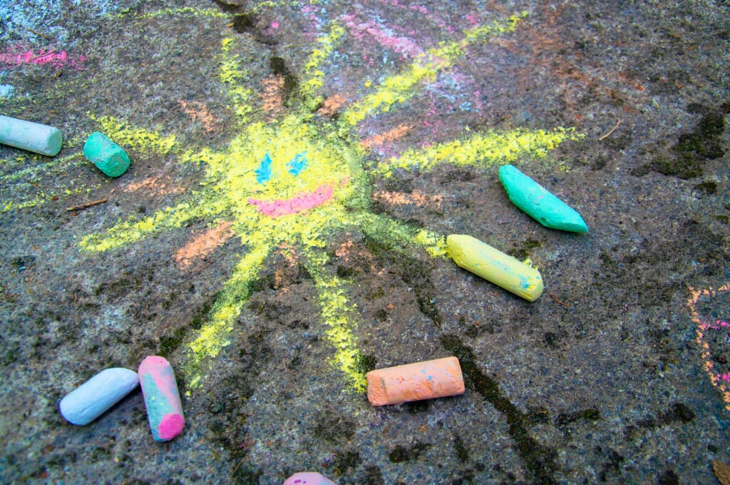 Chalk painting of a happy  sun on the pavement
