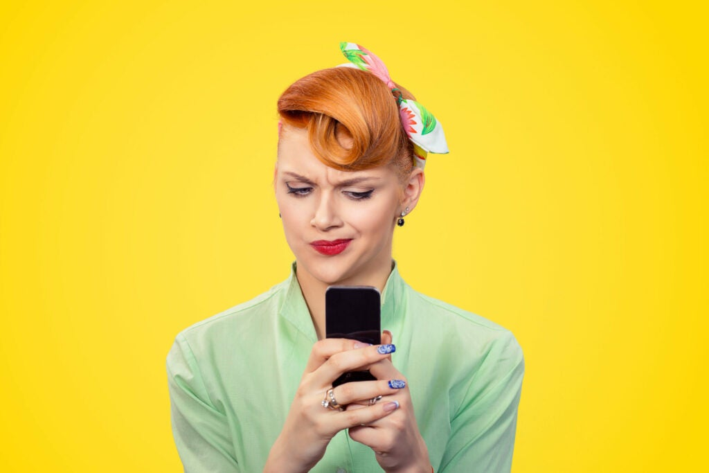 unhappy serious woman looking at texting on phone displeased with conversation