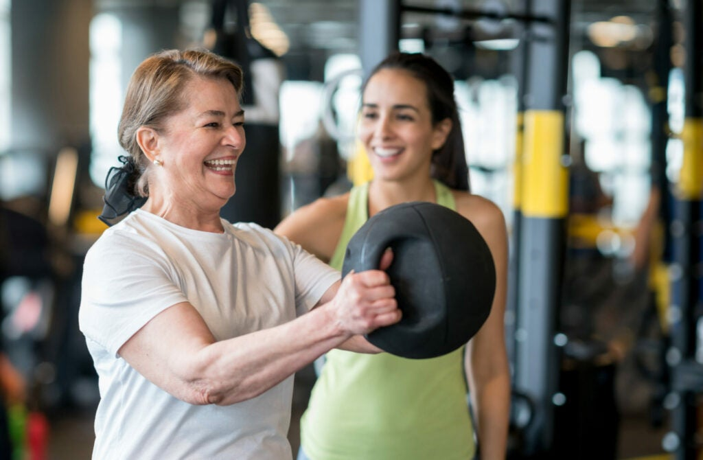 Adult woman exercising at the gym with a personal trainer