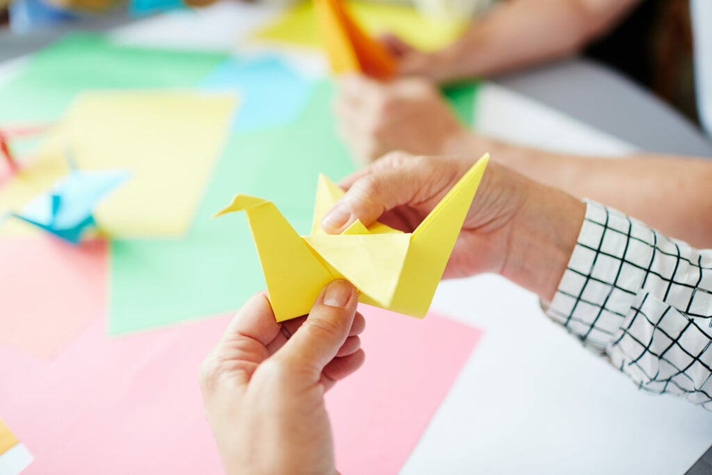 female hands folding sheet of yellow paper while making origami bird