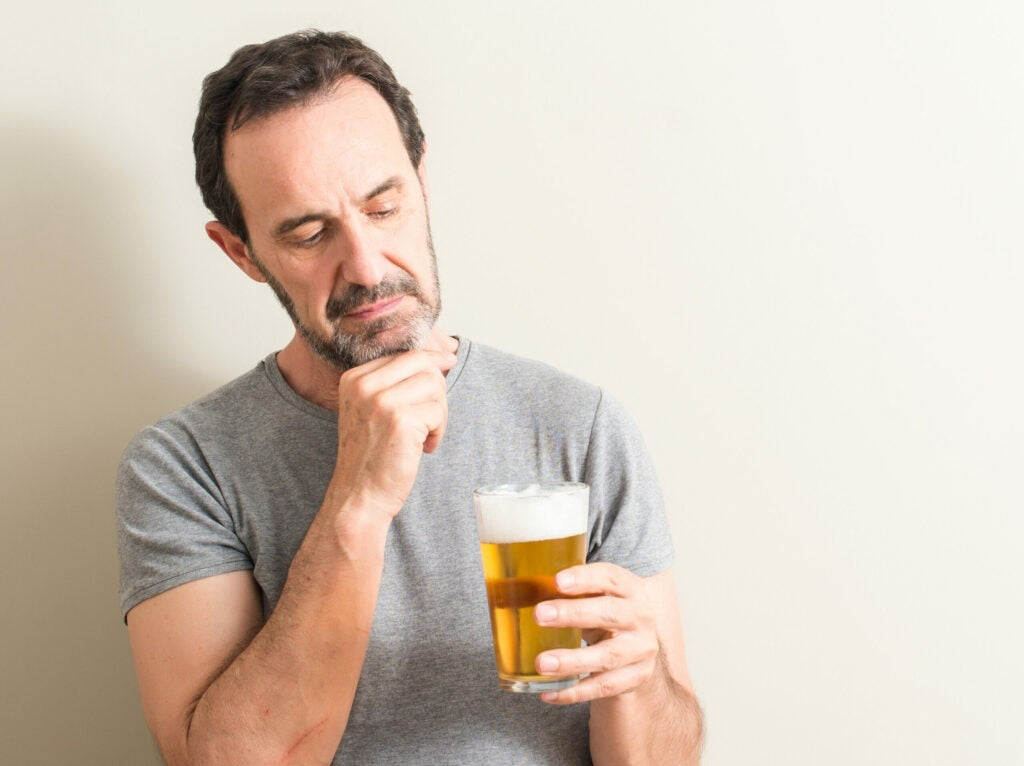 Senior man drinking beer serious face thinking about question, very confused idea