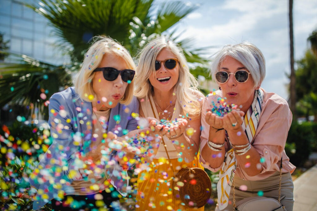 Cheerful senior women celebrating by blowing confetti in the city