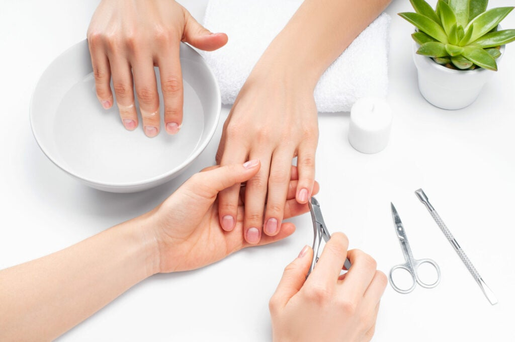 Beautiful woman's hands with perfect manicure. Manicurist master makes manicure