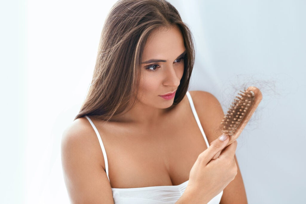 Upset Woman Holding Brush With Hair, Hair Falling Out. High Resolution