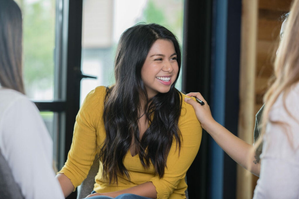 Hispanic woman smiling during support group therapy meeting