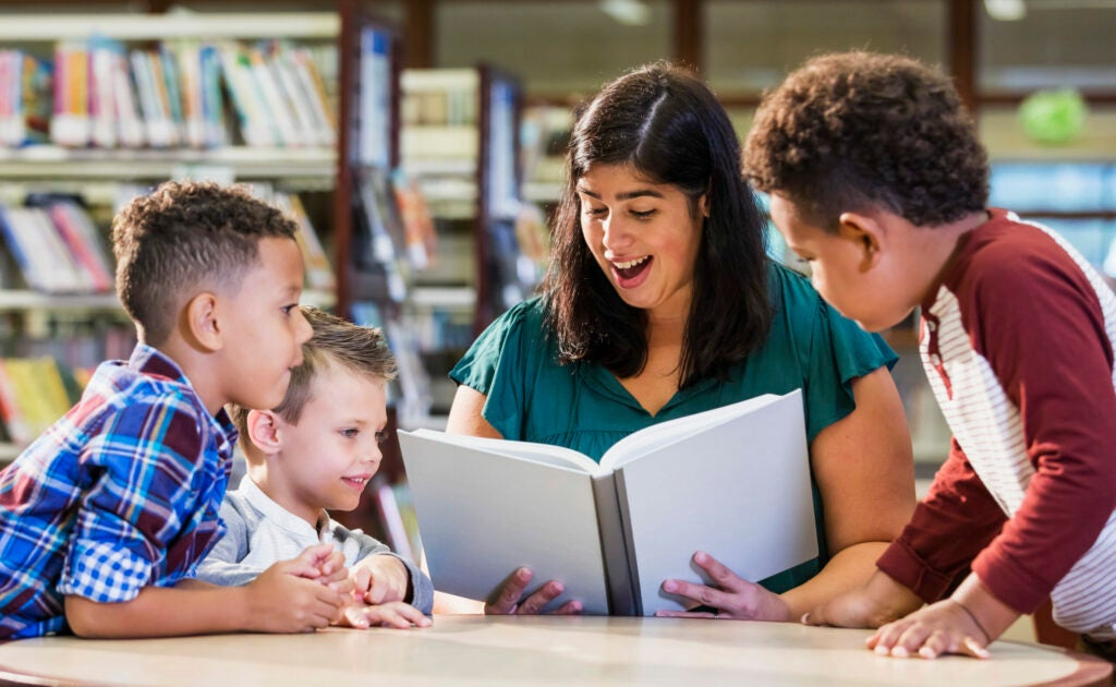 Hispanic teacher with three boys in library reading book