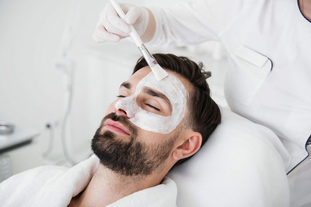 Cosmetologist using brush while putting white clay mask on male face