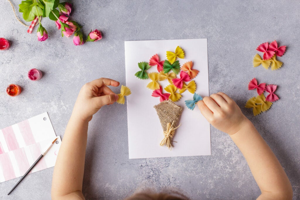 Paper crafts for mother day, 8 march or birthday. Small child doing a bouquet of flowers out of colored paper and colored pasta for mom. Simple gift idea. c