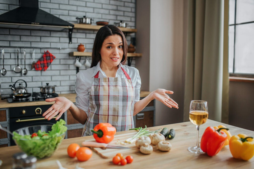 Confused young woman sit at table in kitchen