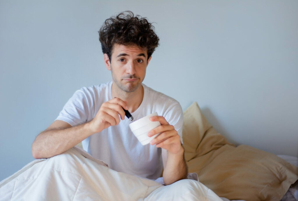Young man eating ice cream while resting in the bed at home. Indoors