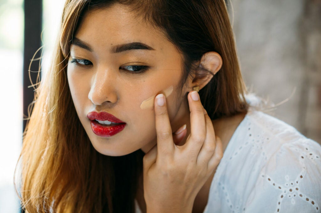 Closeup young Asian woman with red lips applying corrector on face on blurred background