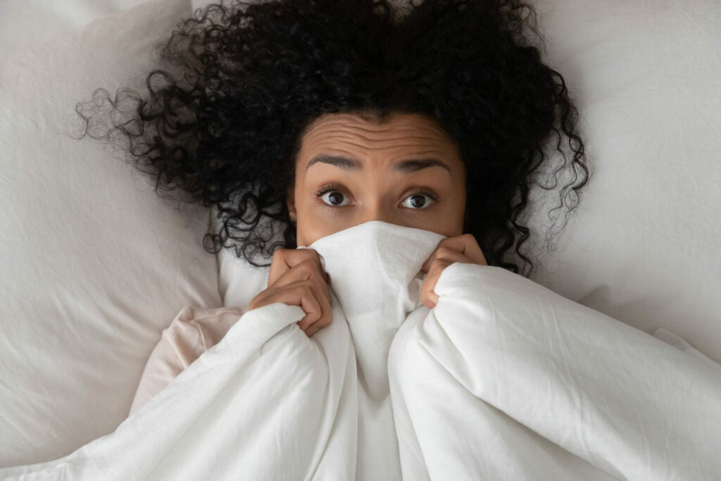 Surprised funny african girl in bed covering face with blanket