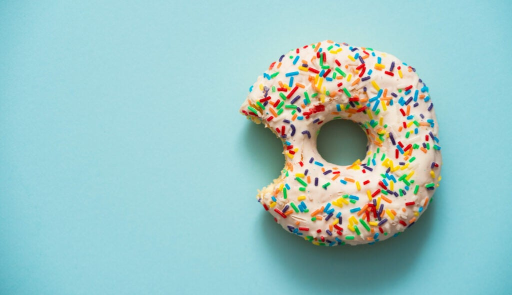 One bite missing of donut on blue background.