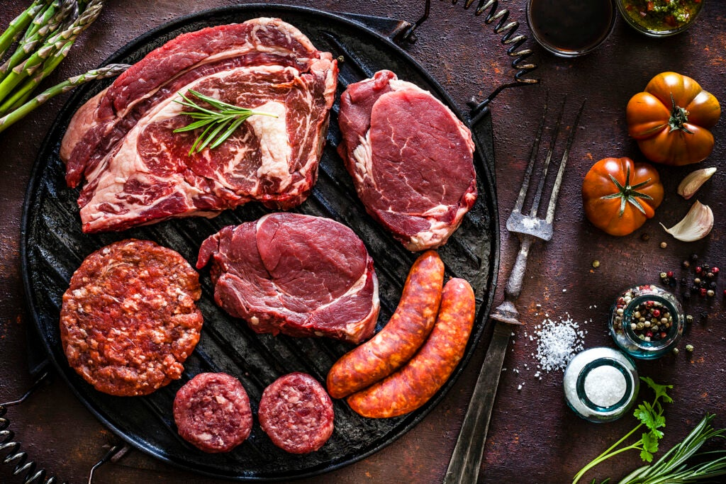 Various cuts of raw meat shot from above on a cast iron grill