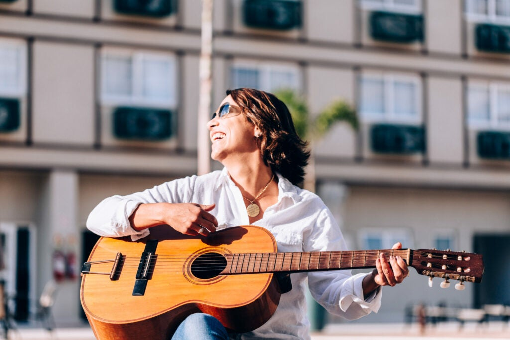 Mid adult woman playing acoustic guitar