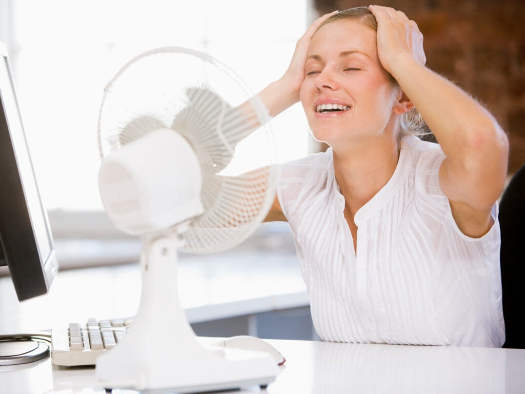 Woman cools self with fan.