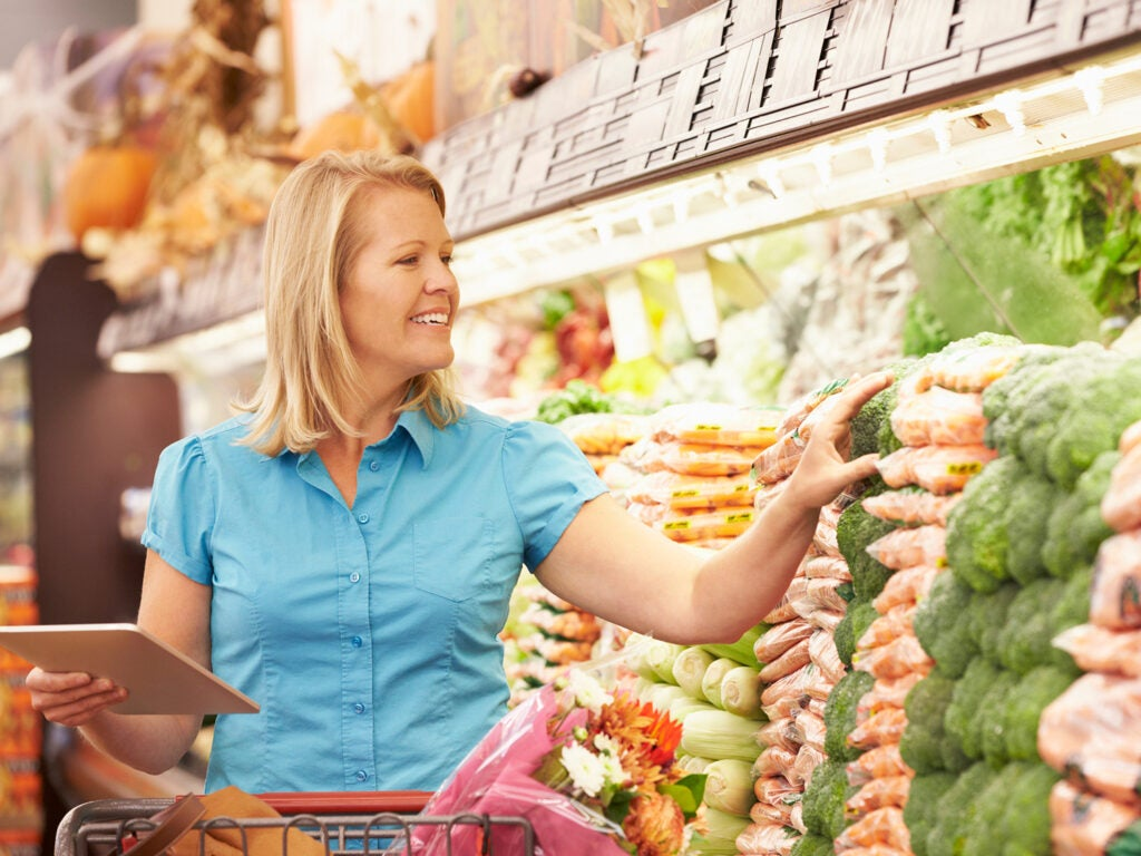 Woman shops for vegetables in grocery store.
