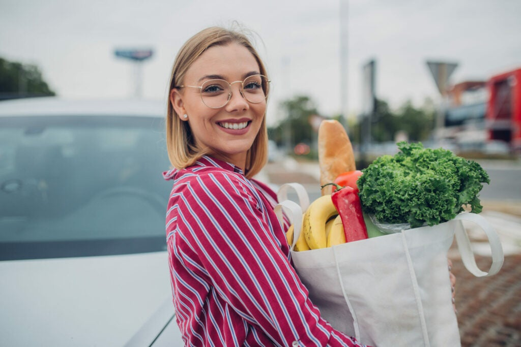 Young woman with eyeglasses standing with reusable bag on parking lot after groceries shopping