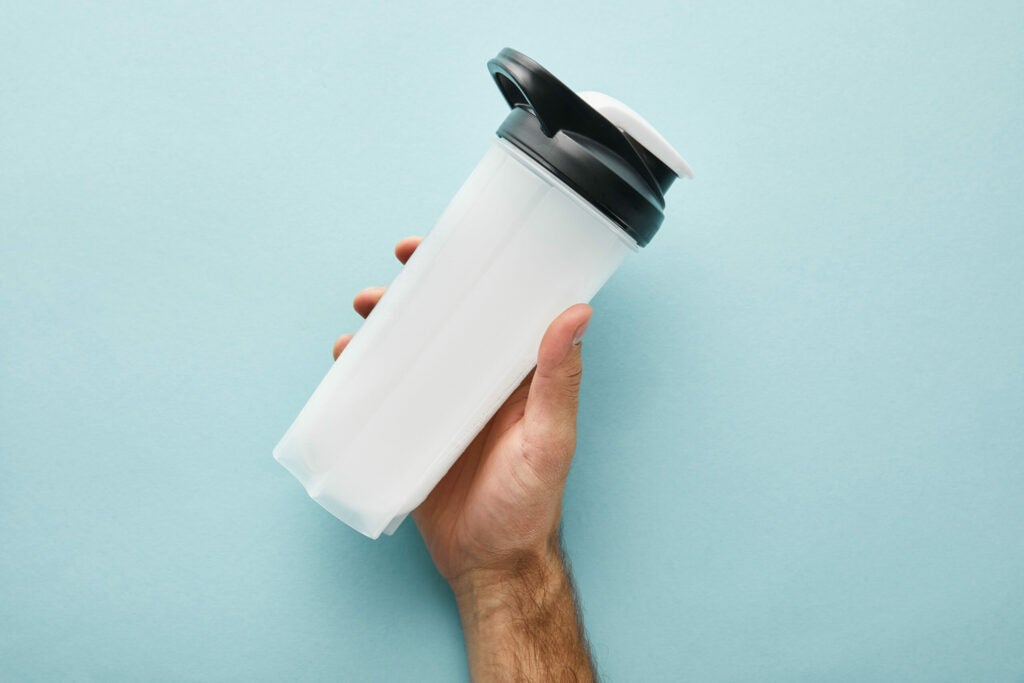 cropped view of man holding sports bottle with protein shake on blue