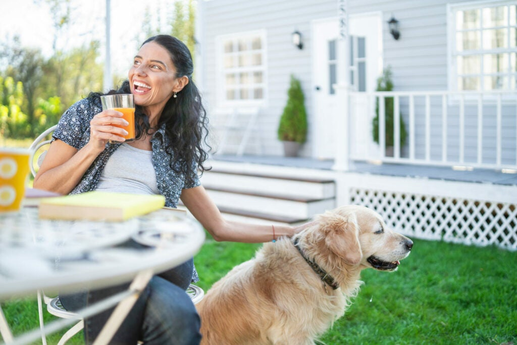 Smiling mid adult woman sitting with her golden retriever on front yard and reading a book