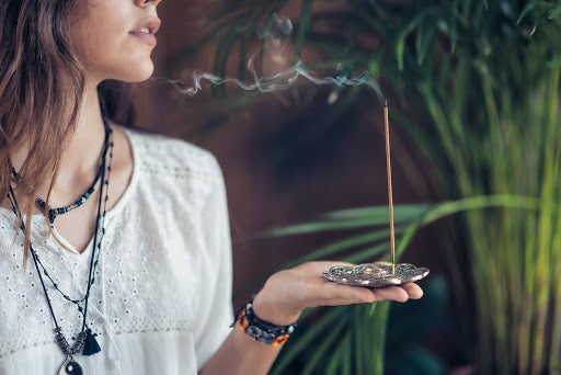 young girl relaxing and enjoying incense stick