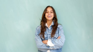 Horizontal portrait of a young woman laughing with arms crossed in relaxed pose against blue background