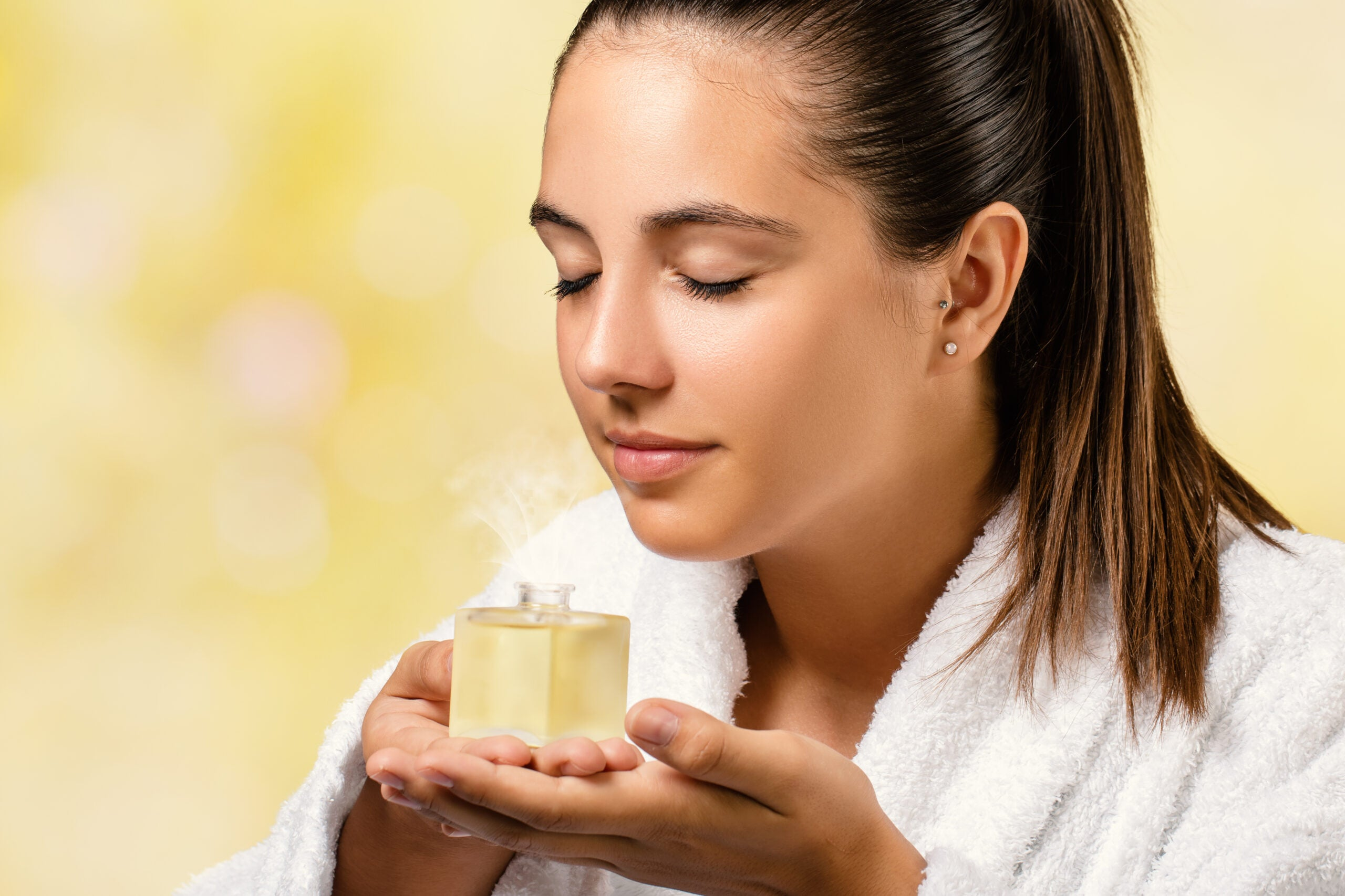 Young woman smelling essential oil fragrance.