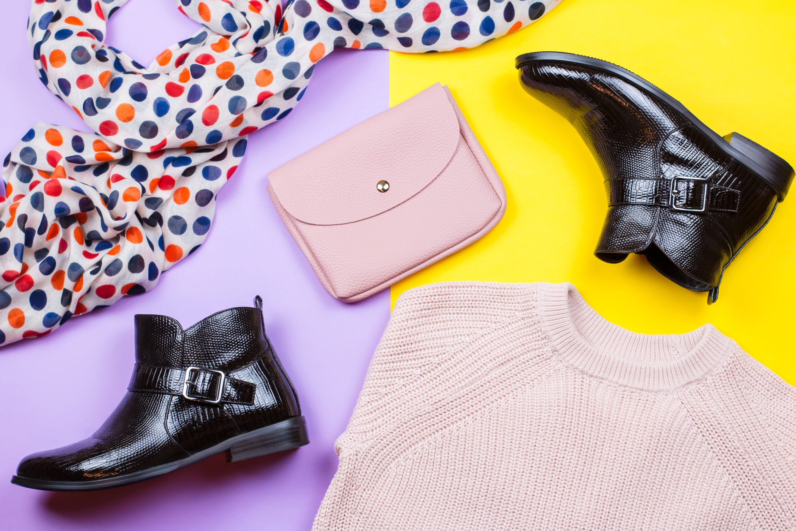 Trendy female autumn clothing. Stylish ankle boots, pink sweater, pink purse and printed scarf on a bright background