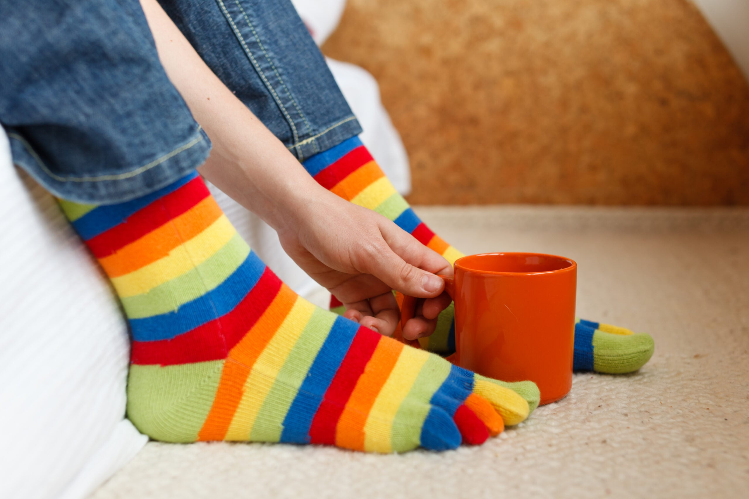 Feet in colorful socks and hand holding coffee cup, concept of home laziness and comfort