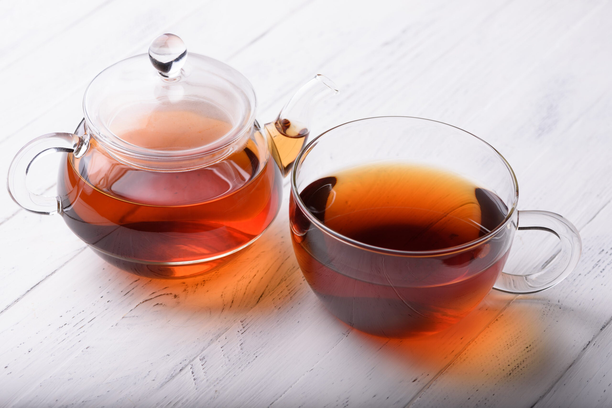 Glass teapot and cup with hot black tea