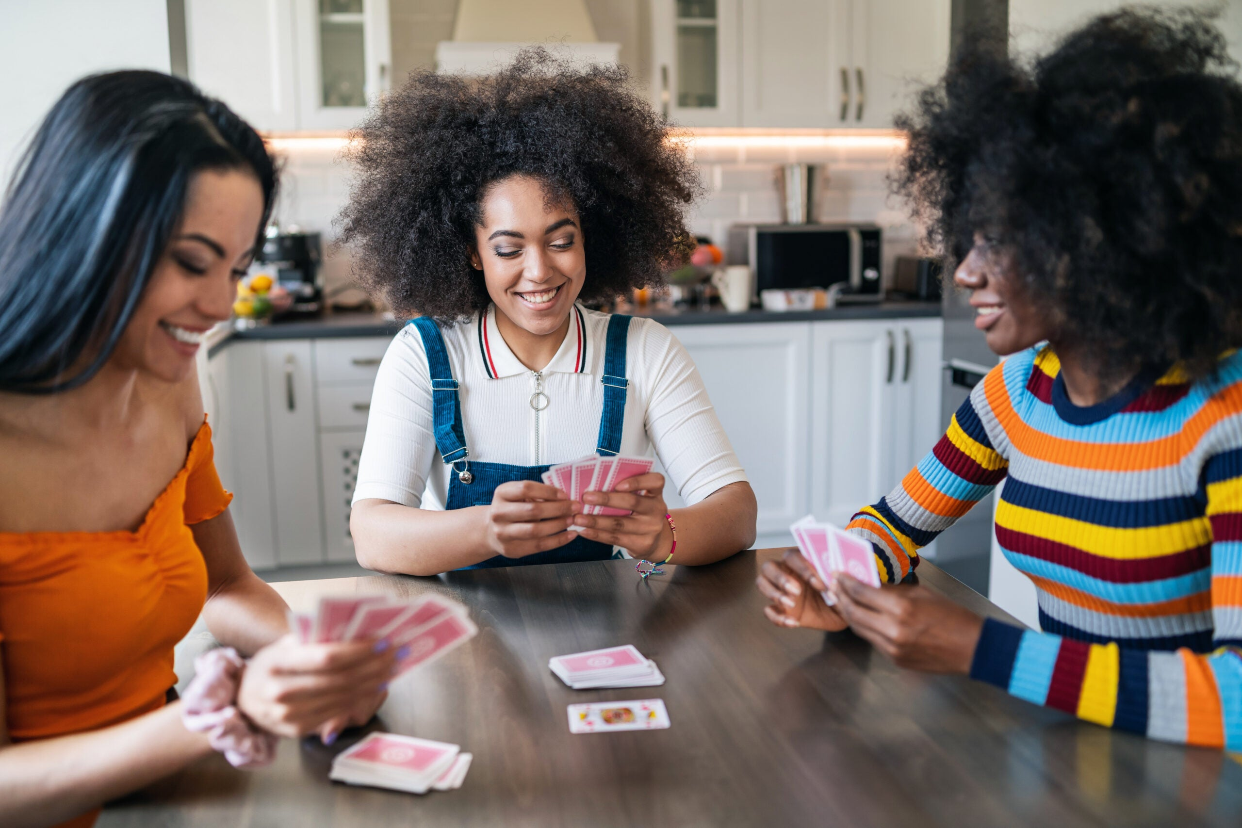 Three girls at home playing cards