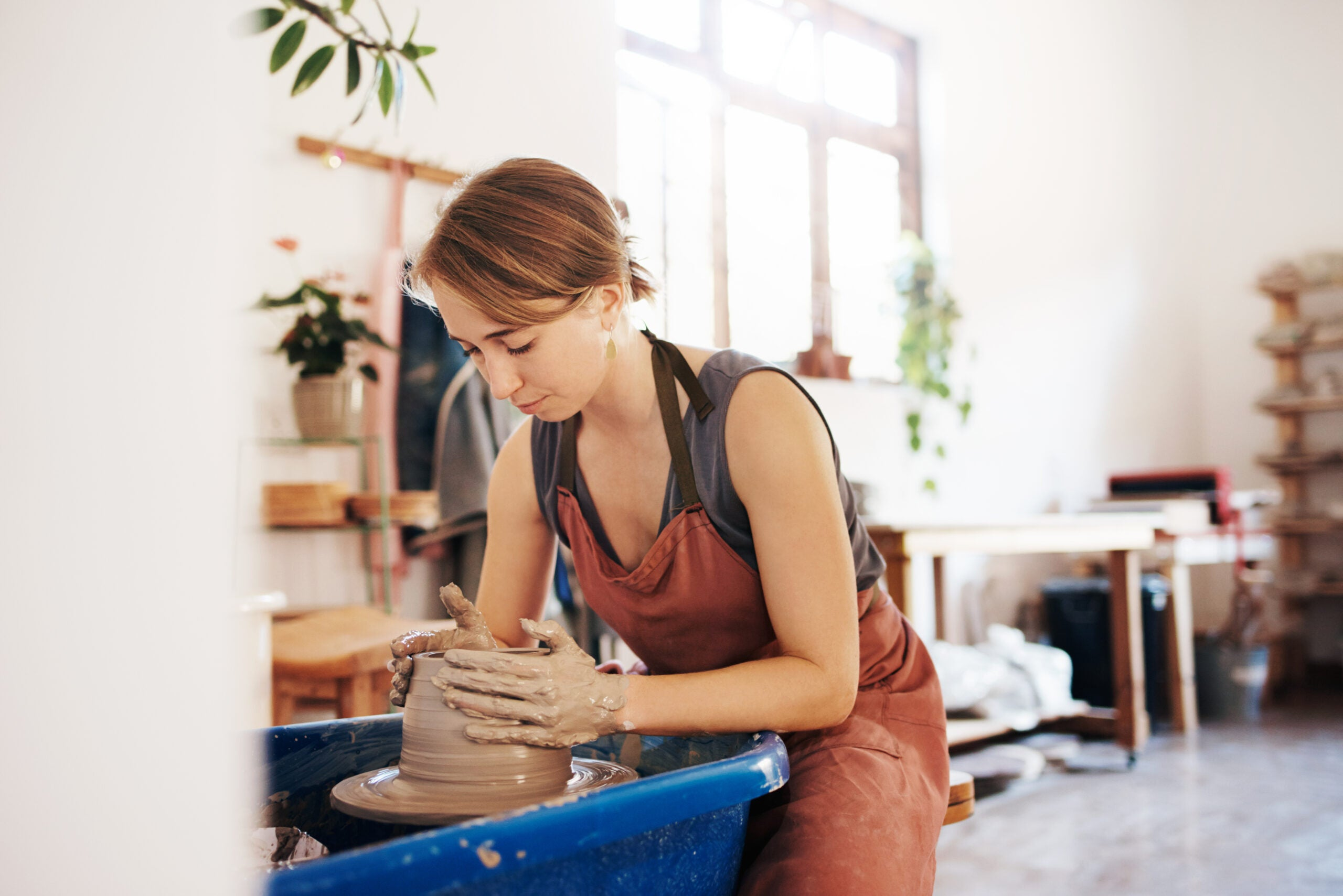 Shot of a woman molding clay on a pottery wheel