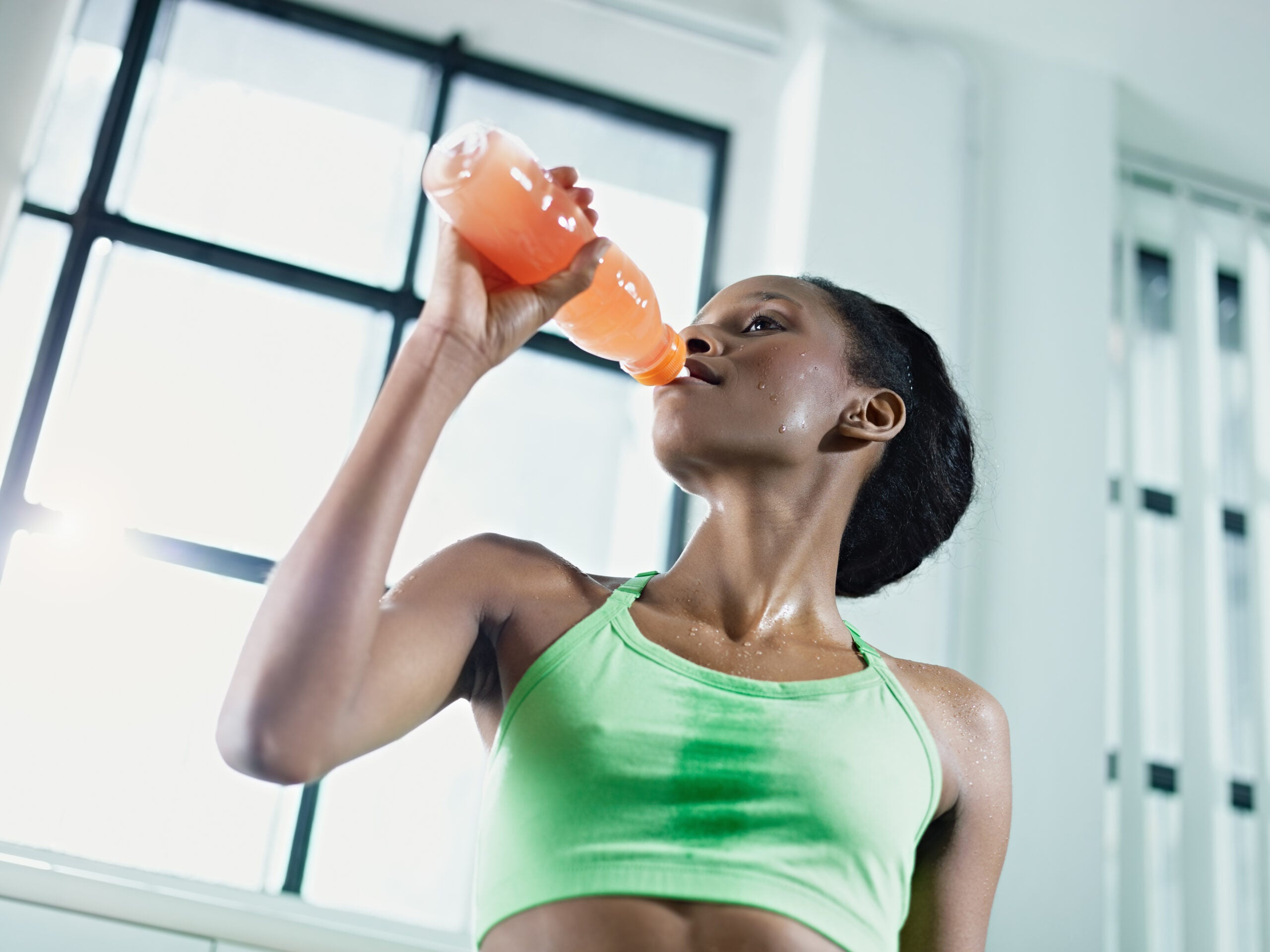 African American woman drinking an energy drink at the gym