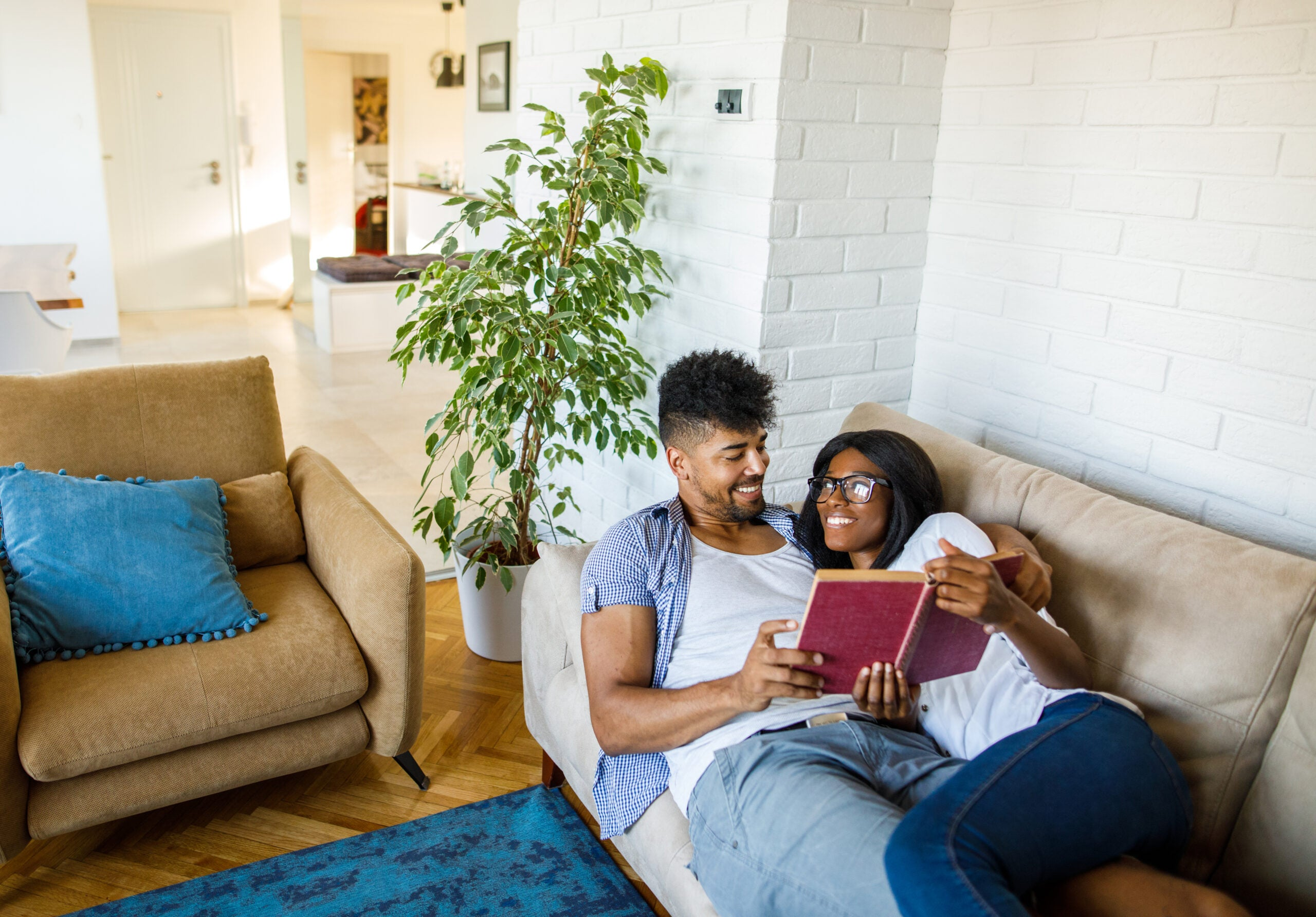 Romantic couple resting on sofa and reading a book