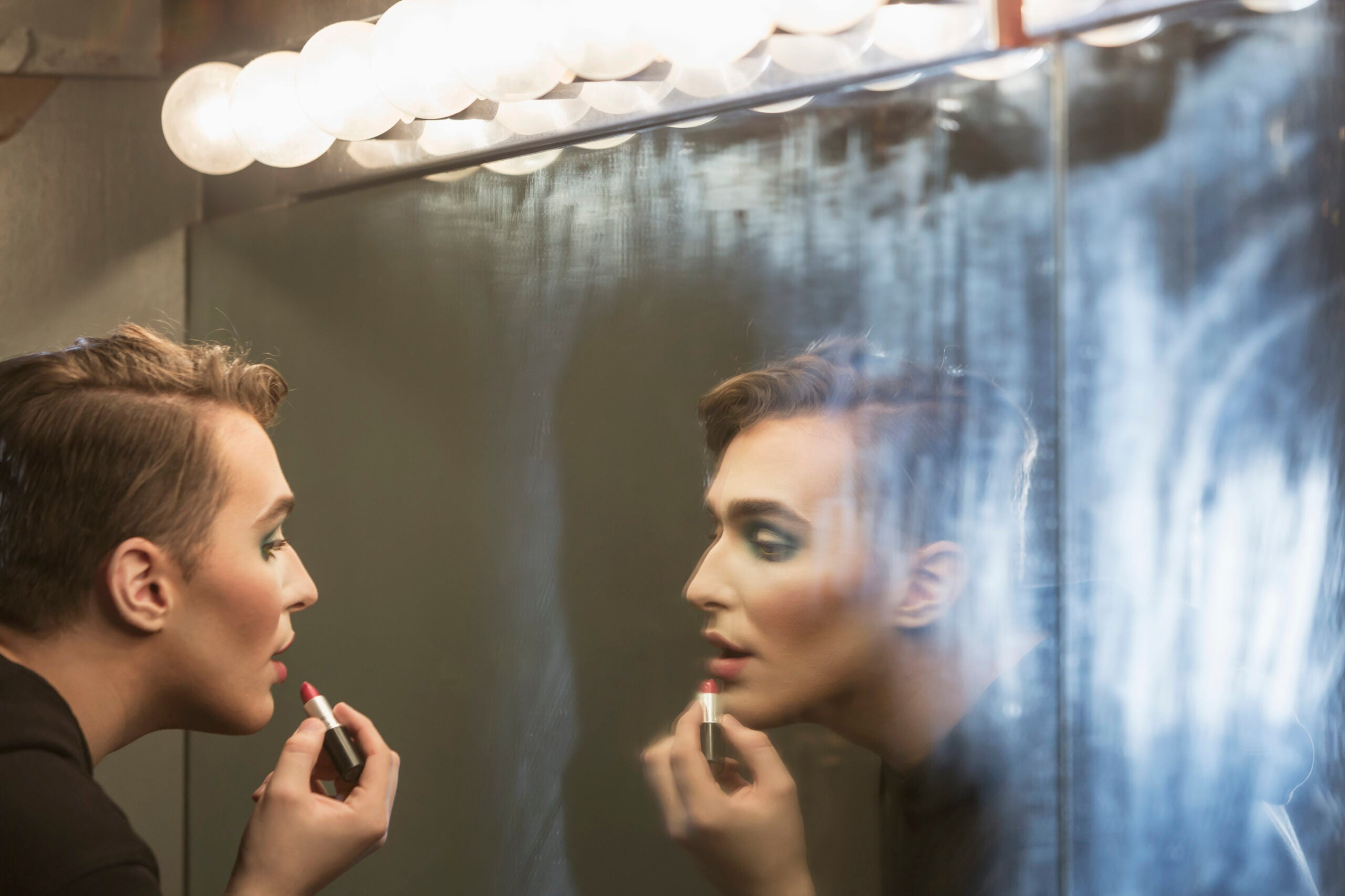 Young man in dressing room applying make-up - drag queen