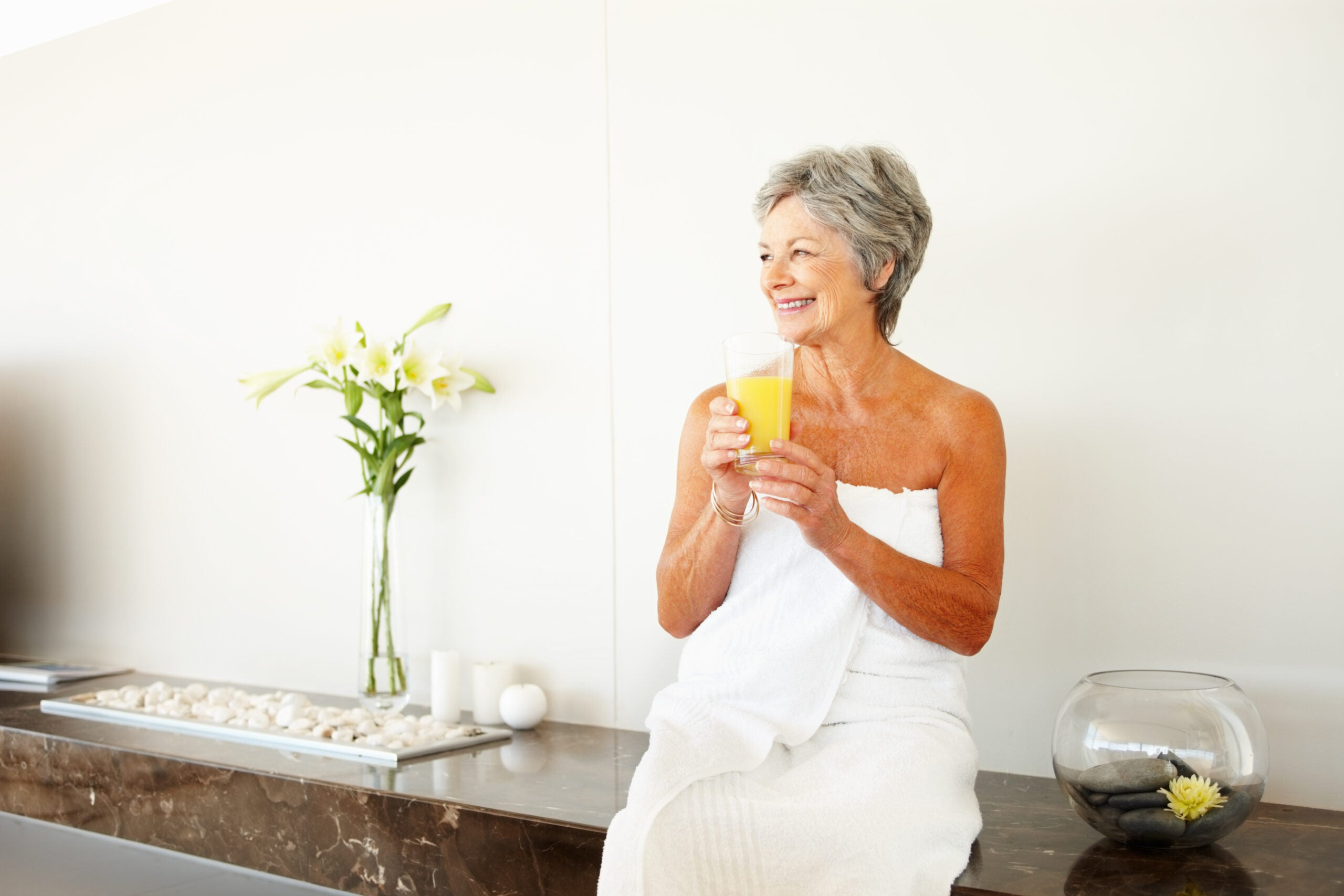 Happy senior woman wrapped in towel holding a glass of juice