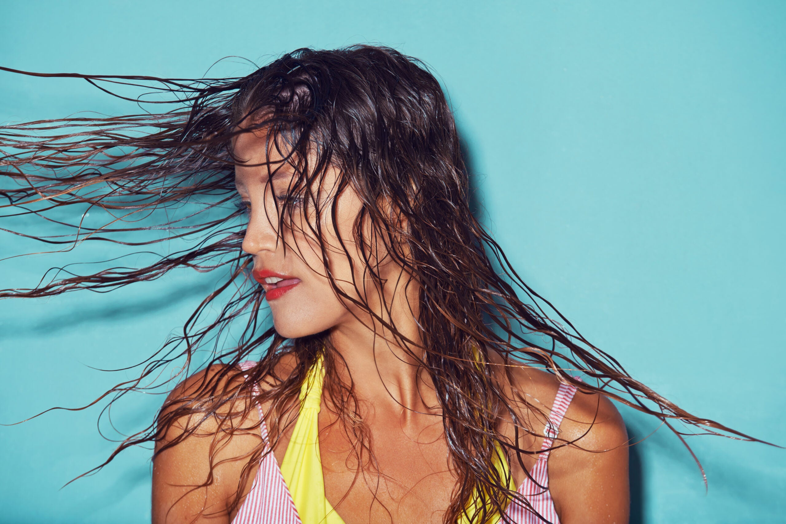 Shot of a young woman flipping her wet hair against a blue background