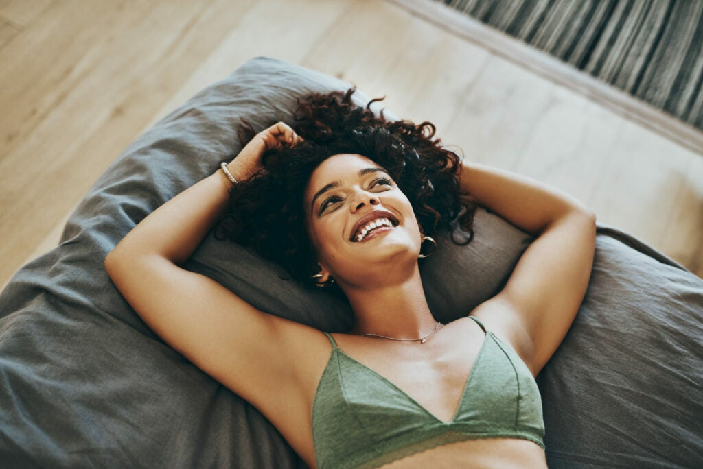 Shot of a young woman wearing underwear while relaxing in her bedroom