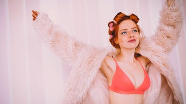 Young woman having fun in underwear and fur coat whilst getting ready to go out