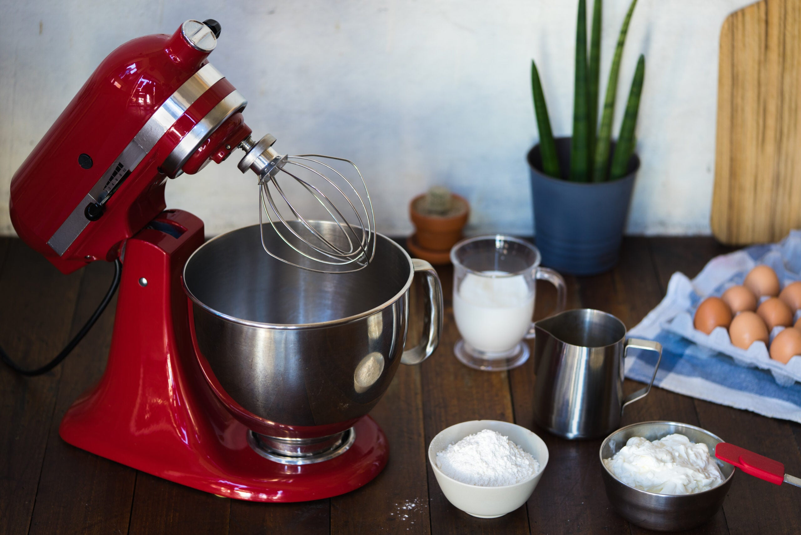 Open red standing mixer on wooden table