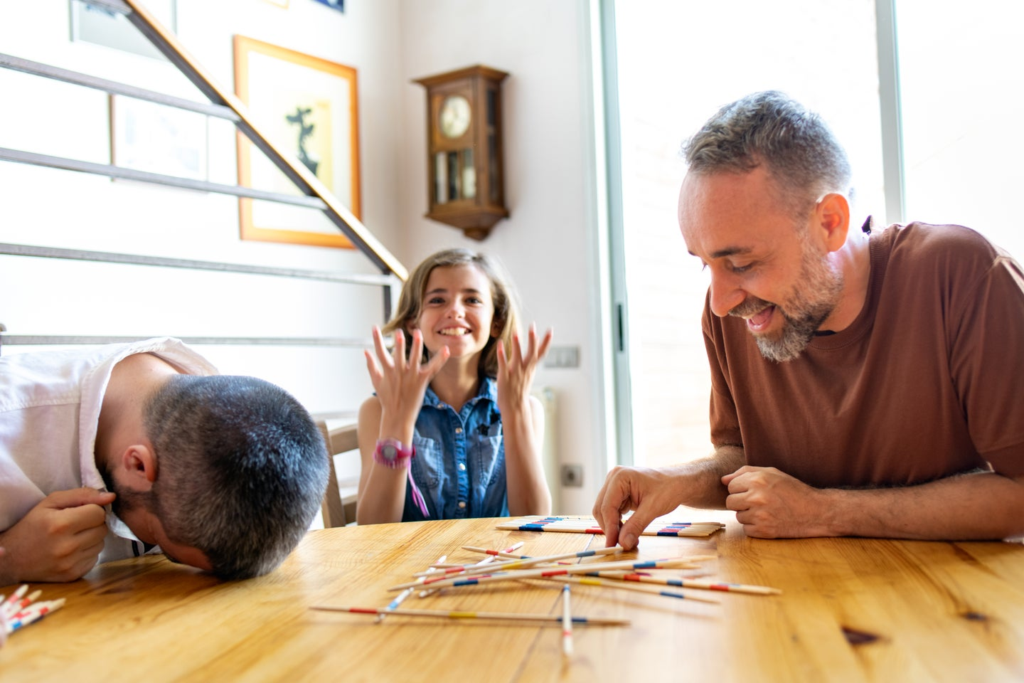 parents playing Pick Up Sticks with their kids