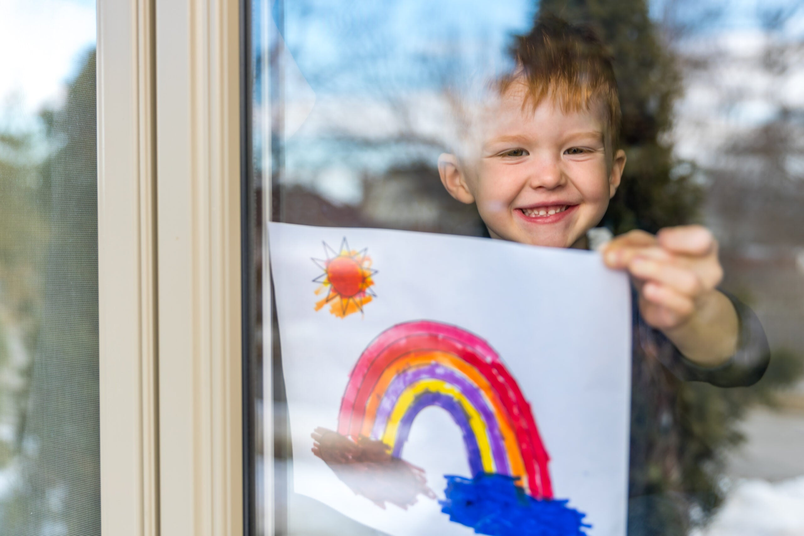 Young Boy sticking his drawing on home window during the Coronavirus Covid-19 crisis, Many people are putting a rainbow to tell neighbors that people inside this house are ok. #Stay at home.